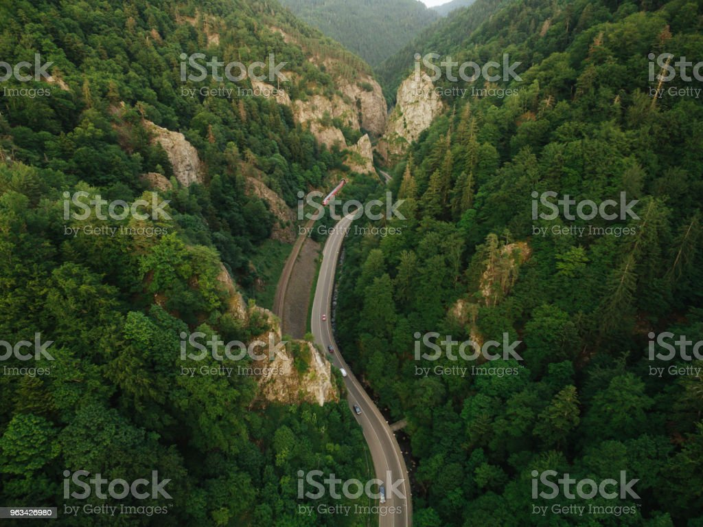 aerial view of road in beautiful mountain forest with railroad - Zbiór zdjęć royalty-free (Balustrada - Granica)