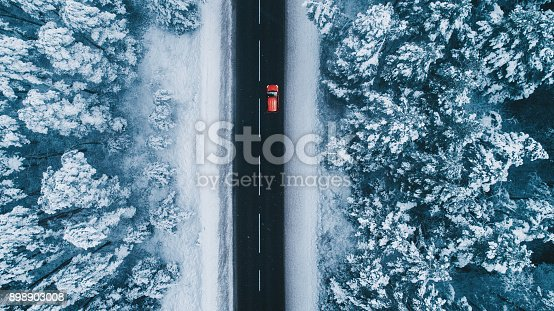 istock Aerial view of road in winter with red car on it 898903008