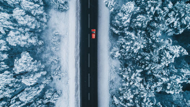 Aerial view of road in winter with red car on it stock photo