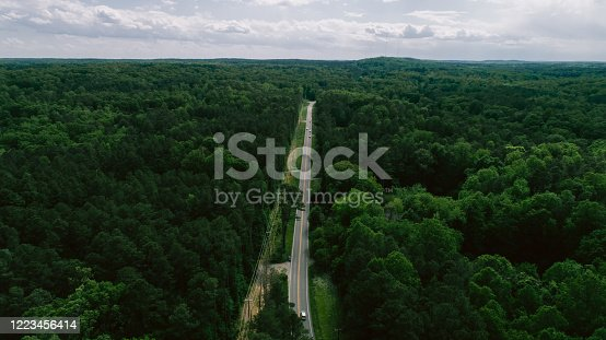 888361900 istock photo Aerial View of Road Through Forest in the Spring 1223456414