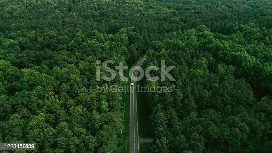 888361900 istock photo Aerial View of Road Through Forest in the Spring 1223456539