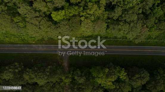 888361900 istock photo Aerial View of Road Through Forest in the Spring 1223456643