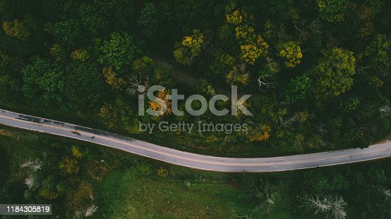 1042711480 istock photo Aerial View of Road through Forest 1184305819
