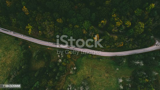 1042711480 istock photo Aerial View of Road through Forest 1184305888