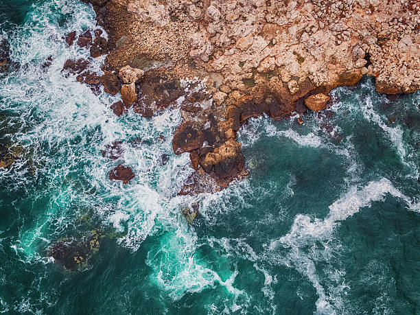Aerial view of rocky coastline and crashing waves stock photo
