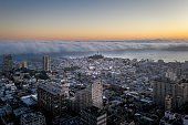 Aerial view of sunrise in San Francisco, California. View of Nob Hill and Coit Tower in the distance. Heavy curled fog is rolling in across the San Francisco Bay looking like a tidal wave . Famous buildings fill the horizon as the sun comes up and the fog rolls in. A luxury cruise ship is in the Bay.