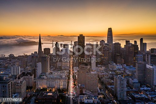 Aerial view of sunrise in San Francisco, California. View of Nob Hill, the financial district, iconic buildings and the well known California Street with the Bay Bridge at the end of the street. Well know buildings line the street. Treasure island and the San Francisco Bay have fog rolling across. Twinkling lights across the city skyline.