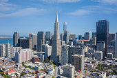 An aerial view of San Francisco on a beautiful blue sky day. The city skyline is filled with recognizable skyscrapers. The San Francisco Bay is visible in the background.