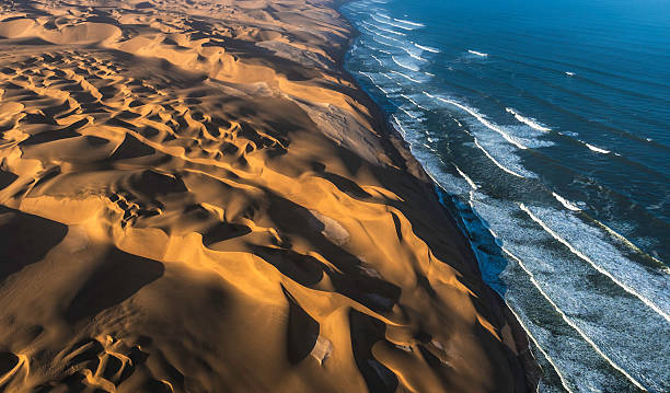 Aerial View of Sand Dunes and Ocean Aerial view of the sand dunes of the Namib Desert colliding with the Atlantic Ocean, Namibia. namibia stock pictures, royalty-free photos & images