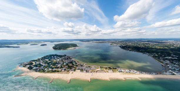 Aerial view of Sandbanks, Poole Harbour and Brownsea Island Aerial view of Poole Harbour and Brownsea Island and Dorset coastline on a sunny day. groyne stock pictures, royalty-free photos & images