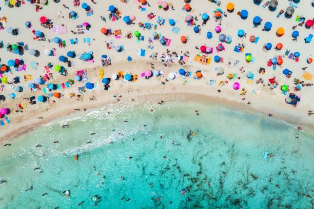Luftaufnahme des sandigen Strandes mit bunten Sonnenschirmen, Menschen schwimmen im Meer, die Bucht mit transparenten blauen Wasser in sonniger Morgen im Sommer. Reisen Sie in Mallorca, Balearen, Spanien. Ansicht von oben. Landschaft – Foto