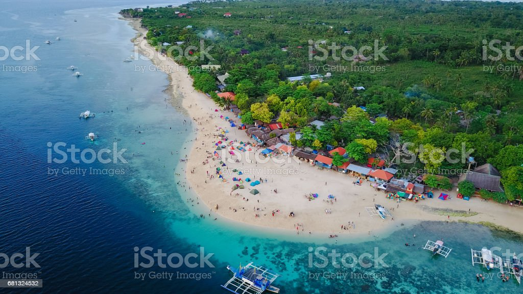 Aerial view of sandy beach with tourists swimming in beautiful clear sea water of the Sumilon island beach landing near Oslob, Cebu, Philippines. - Boost up color Processing. royalty-free stock photo