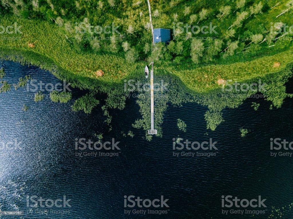 Luftaufnahme des SAUNAHAUS am Ufer Sees. Holzsteg mit Fischerbooten. - Lizenzfrei Alt Stock-Foto
