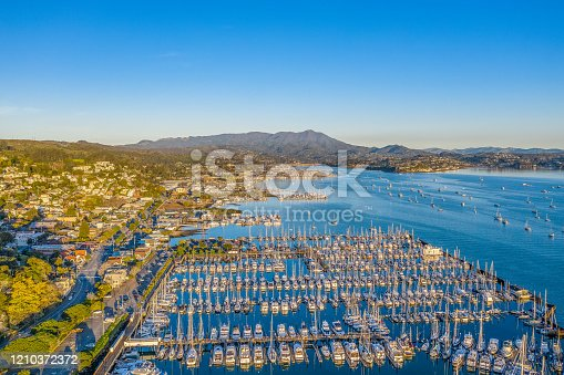 An aerial view of Sausalito on a golden morning. The sun is shining on the hillside and a view of the marina and bay.