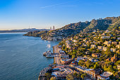An aerial view of Sausalito on a golden morning with the Golden Gate Bridge peaking over the hillside.