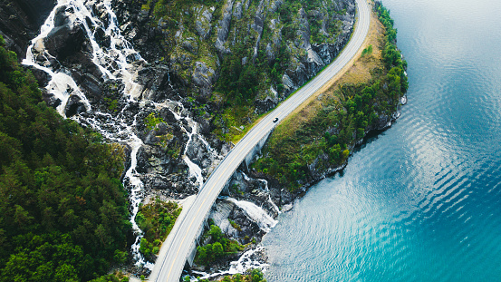 Drone panoramic photo of the car driving through picturesque road above the huge waterfall near the fjord in South Norway