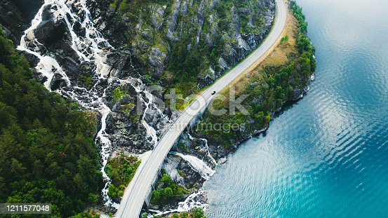 istock Aerial view of scenic mountain road with car, sea and waterfall in Norway 1211577048