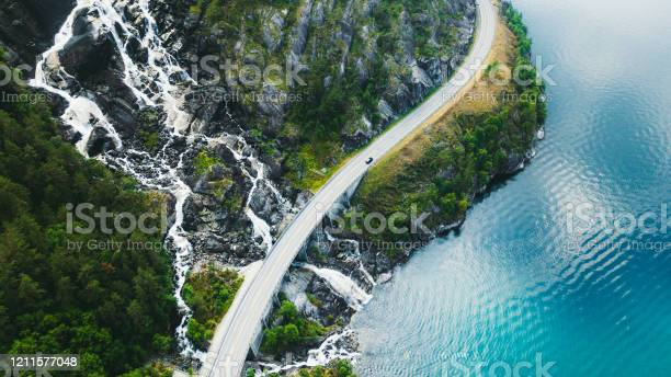 Photo of Aerial view of scenic mountain road with car, sea and waterfall in Norway