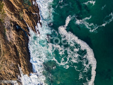 Aerial view of beautiful seascape. Waves are crashing on rocky coastline. Scenic view of ocean.