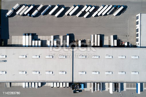 Aerial view of rows of semi trucks, tankers and a large warehouse.