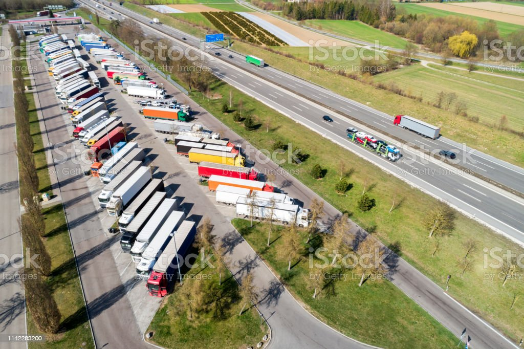 Aerial view of a multiple lane highway and a large truck stop with...