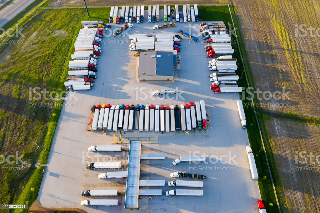 Aerial view of a large truck stop with rows of parked semi trucks.
