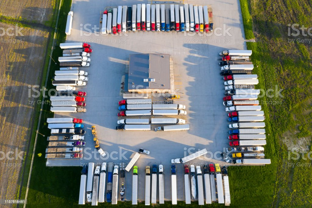 Aerial view of a large truck stop with rows of parked semi trucks....