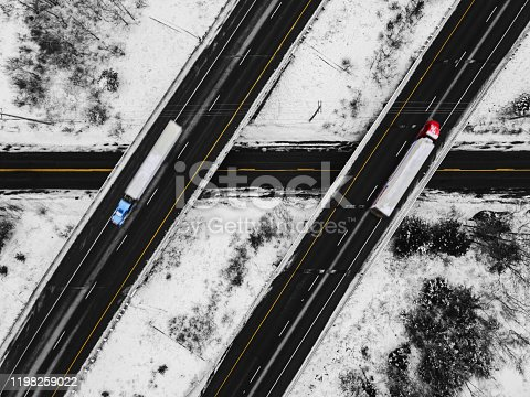 Aerial drone view of semi trucks travelling on a multi-lane highway.