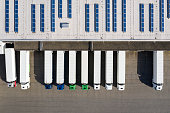 Aerial view of cargo containers, semi trailers, industrial warehouse, storage building and loading docks, renewable energy plants, Bavaria, Germany