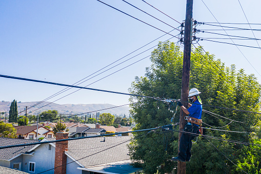 A technician working on the lines in a residential neighborhood
