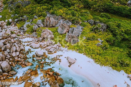 Aerial view of Seychelles tropical Marron beach at La Digue island. White sand beach with turquoise ocean water and granite rocks.