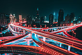 Aerial view of road intersection in Shanghai at night, with blurred motion