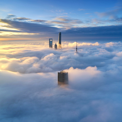 Aerial view of Shanghai skyline on thick cloud at morning, China.