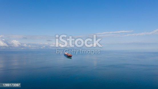 istock Aerial view of single big cargo ship on sea over sunny blue sky 1269173397