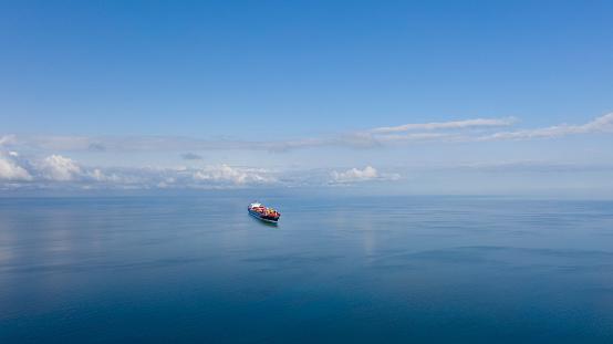 High angle view of single big cargo ship on sea over sunny blue sky