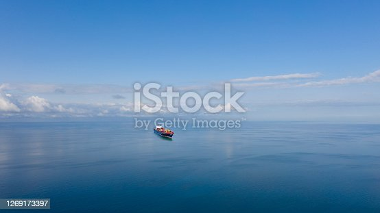 istock Aerial view of single big cargo ship on sea over sunny blue sky 1269173397