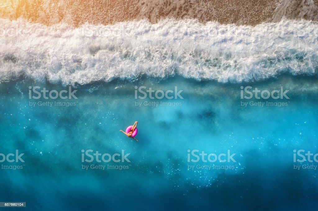 Aerial view of slim woman swimming on the pink swim ring in the transparent turquoise sea in Oludeniz,Turkey. Summer seascape with girl, beautiful waves, blue water in sunny day. Top view from drone stock photo