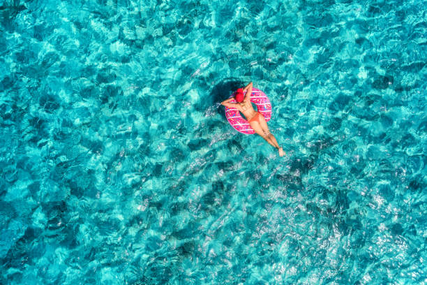 Luftaufnahme der schlanke junge Frau, die am hellen Sonnentag auf die rosa Donut Schwimmring im transparenten blauen Meer schwimmen. Tropische Luft Landschaft mit Mädchen, azurblauen Wasser. Ansicht von oben. Sommer reisen. Urlaub – Foto