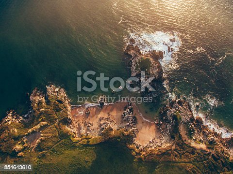 An aerial view of a small rocky beach at sunset