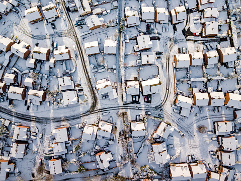 Aerial view of snowed in traditional housing suburbs in England.