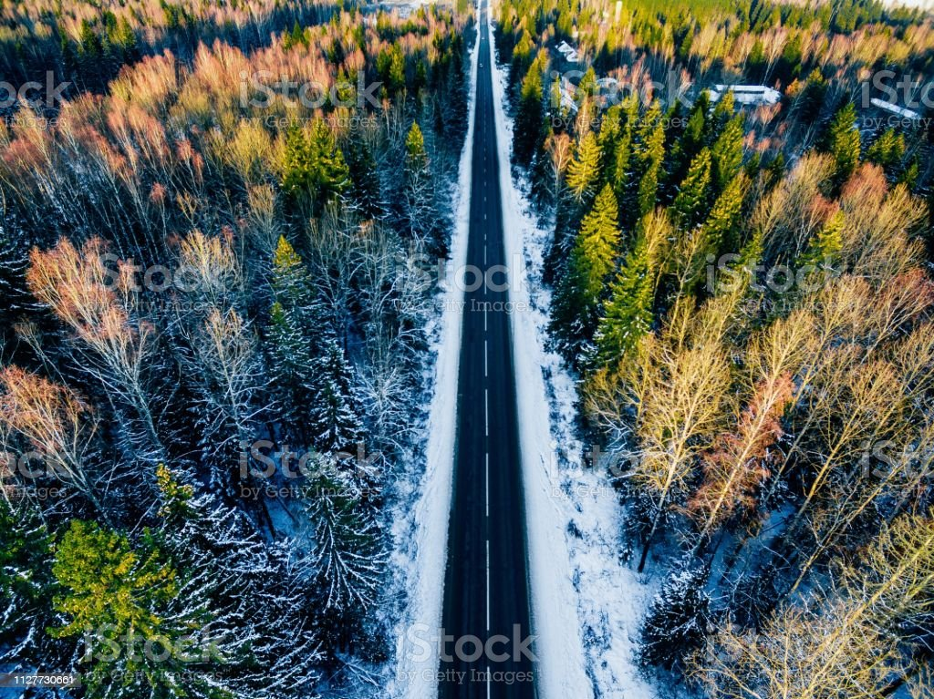 Aerial view of snowy forest with a road. Captured from above with a...