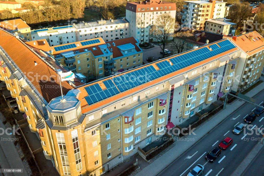 Vista aérea del sistema de paneles fotovoltaicos solares en el techo del edificio de apartamentos. Concepto de producción de energía verde ecológica renovable. - Foto de stock de Ahorros libre de derechos