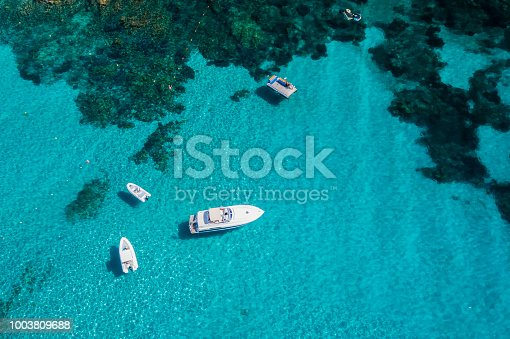 1066331604istockphoto Aerial view of some yachts on an emerald and transparent Mediterranean sea. Emerard coast (Costa Smeralda), Sardinia, Italy. 1003809688