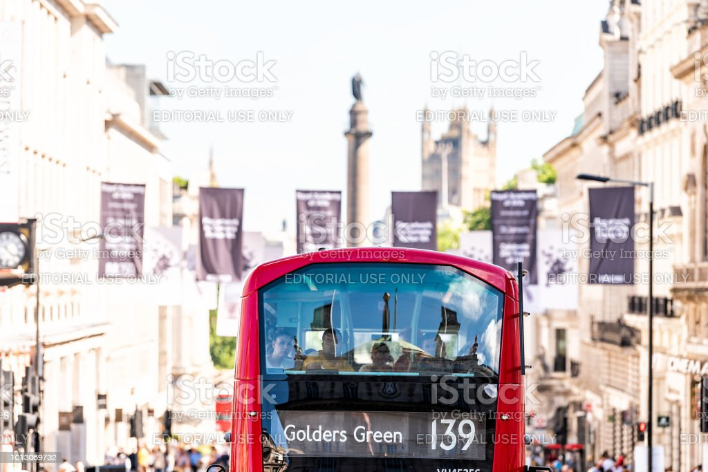 Aerial view of street road with double decker red big bus in center of downtown city, Piccadilly Circus flags, bokeh of Westminster, Golders Green sign stock photo