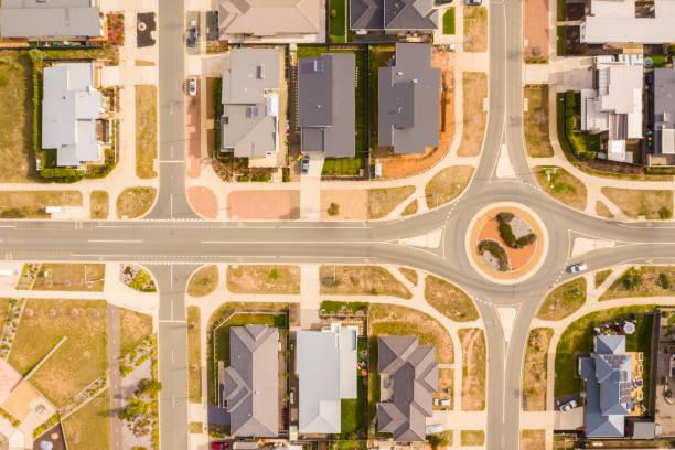 vue aérienne des rues, des toits et d'un rond-point agrémenté de conception d'aménagement paysager dans la banlieue nouvellement établie de coombs à canberra, australie - rond point carrefour photos et images de collection