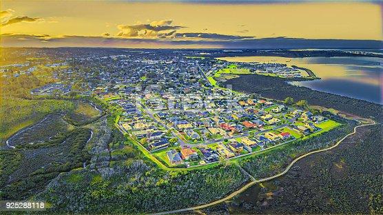 Aerial view of suburb near coastline at sunset - digital artwork