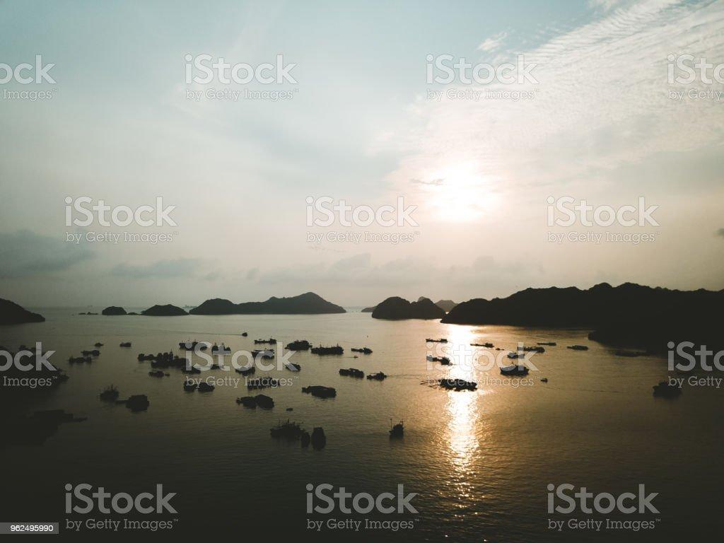 Vista aérea do pôr do sol acima de barcos de pesca e pequenas ilhas perto de Cat Ba no Vietnã - Foto de stock de Aldeia royalty-free