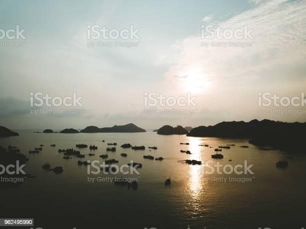 Foto de Vista Aérea Do Pôr Do Sol Acima De Barcos De Pesca E Pequenas Ilhas Perto De Cat Ba No Vietnã e mais fotos de stock de Aldeia