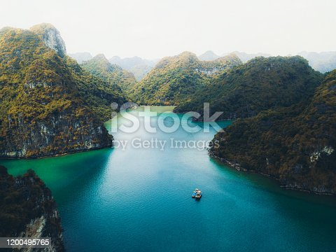Drone panoramic photo of small islands with rainforest, boat and the sea during bright summer sunrise at Halong Bay, North Vietnam