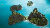 Drone panoramic scenic photo of small islands with rainforest, boat and the sea during bright summer sunset at Halong Bay, North Vietnam
